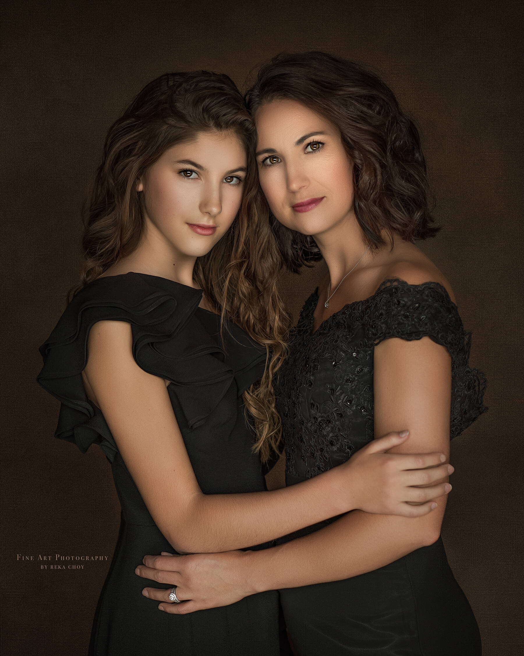 mother and daughter posing for a fine art portrait both dresses in black dress with their hair curled
